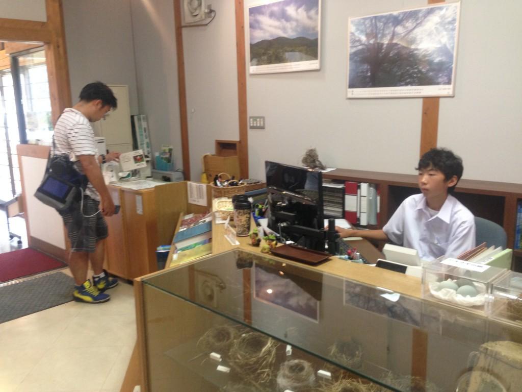 高原の自然館のカウンターで、来館者の対応